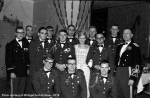 A group dressed in military attire pose for a photo. A woman wearing a corsage stands in the middle of the group.