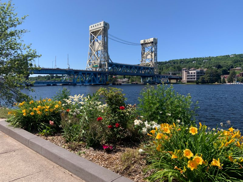Portage Lake Lift Bridge with flowers blooming in the foreground.