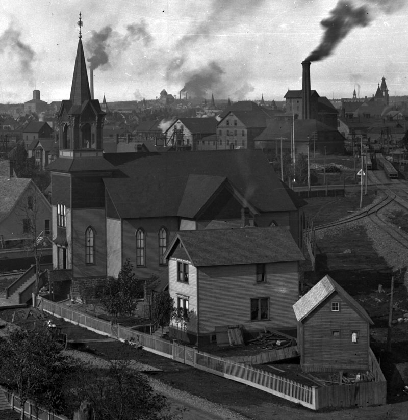 Company housing and Bethlehem Lutheran Church on Agent Street near Calumet, Michigan. The background is dominated by smokestacks, shafthouses, and other industrial workings of the Calumet and Hecla Mining Company.