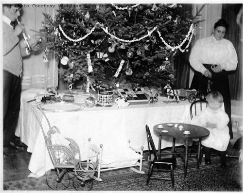 Family gathering around the holiday table. (This image is part of the Gundlach Family Collection and it is available on the Keweenaw Digital Archives)