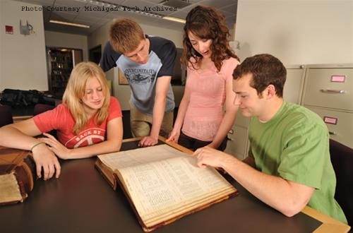 Four archival student assistants look over historical documents in the Michigan Tech Archives Reading Room (2009).