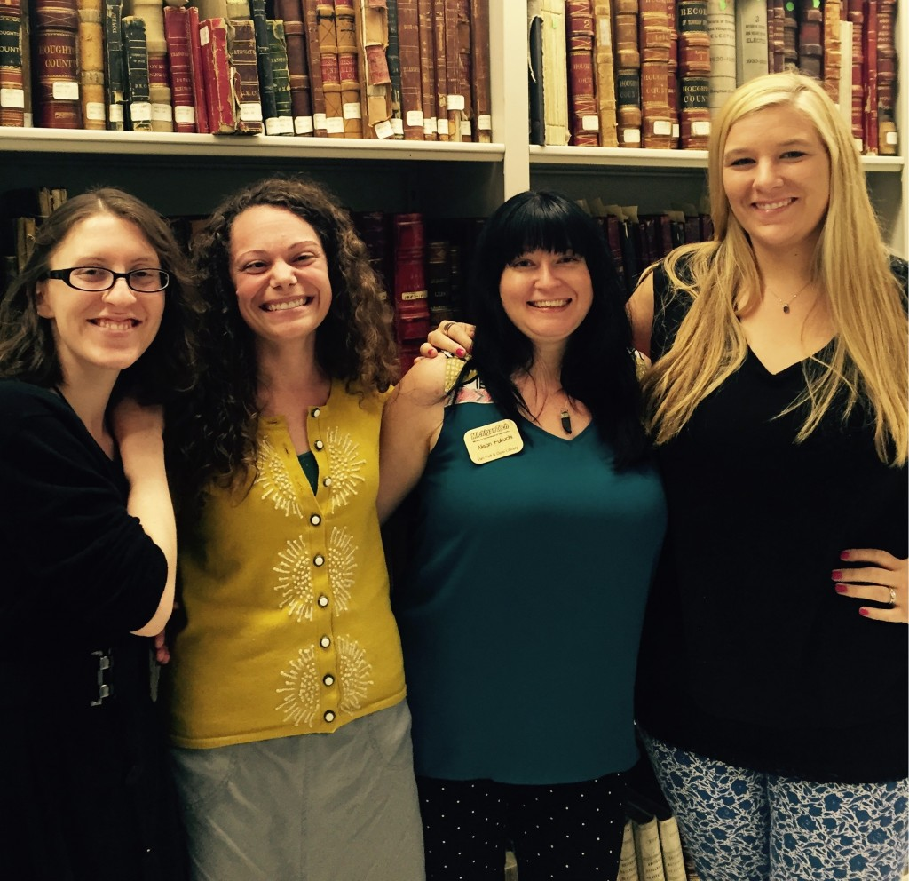 The Archives public services team poses for a final photograph. The ladies stand in front of volumes from the historic state records collection. From left to right are Allyse Staehler, Airen Campbell-Olszewski, Alison Fukuchi, and Georgeann Jukuri.