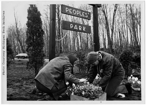 This image shows two students planting flowers at Michigan Tech's People's Park. Built by MTU students, the park was the result of a four-day strike which occured in connection with the Cambodian Invasion and subsequent slayings of students at Kent State and Jackson State. The park was built as a peaceful expression of Tech students' outrage over the above mentioned incidents.