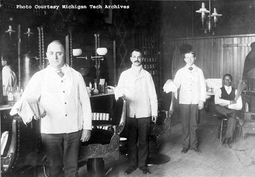 This photograph was taken at a barbershop in Calumet, Michigan by J.W. Nara (date unknown, but presumed early 1900s). It depicts three barbers standing ready and an African-American gentleman seated in the rear of the shop with a broom. The Michigan Tech Archives is currently seeking a project assistant to help us better understand  what collections we have that might shed light on his story and that of many others.