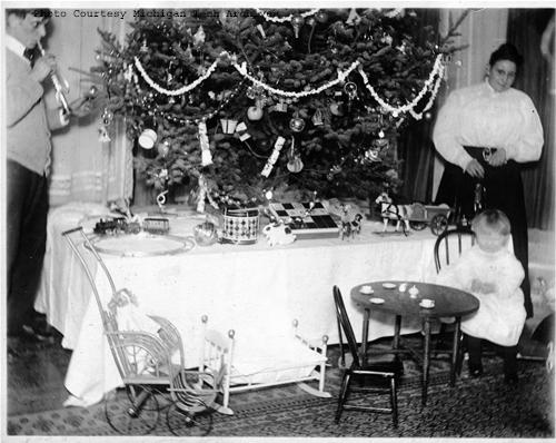 [A man, a woman and a child stand around a decorated Christmas tree, a present table and small child size furniture. From the Herman Gundlach Collection.