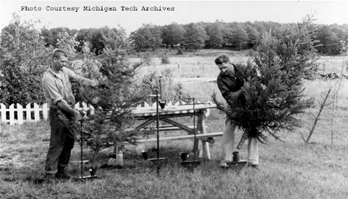 Two men demonstrate how to use the Clouthier tree stands. This photograph is part of the Daily Mining Gazette Photograph Collection.