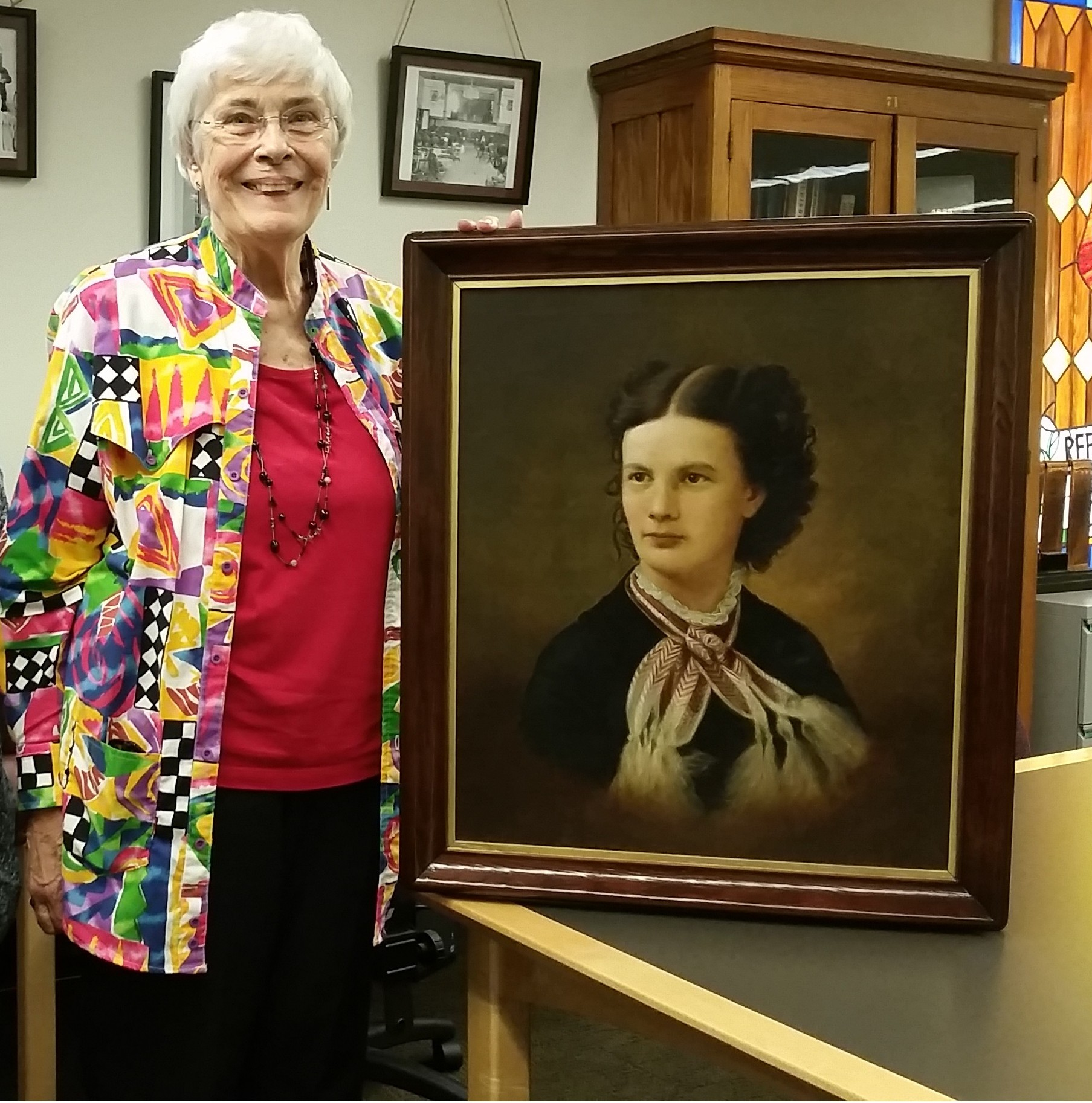 Donor Jane Libby and Archivist Lindsay Hiltunen pose with the framed portrait of Christeen M. Shelden, daughter of local historic figure Ransom B. Shelden. The painting was donated to the Michigan Technological University Archives and Copper Country Historical Collections on Monday, June 20.