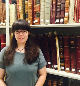 Our new team member, Emily Riippa, poses in the stacks at the end of her first week.