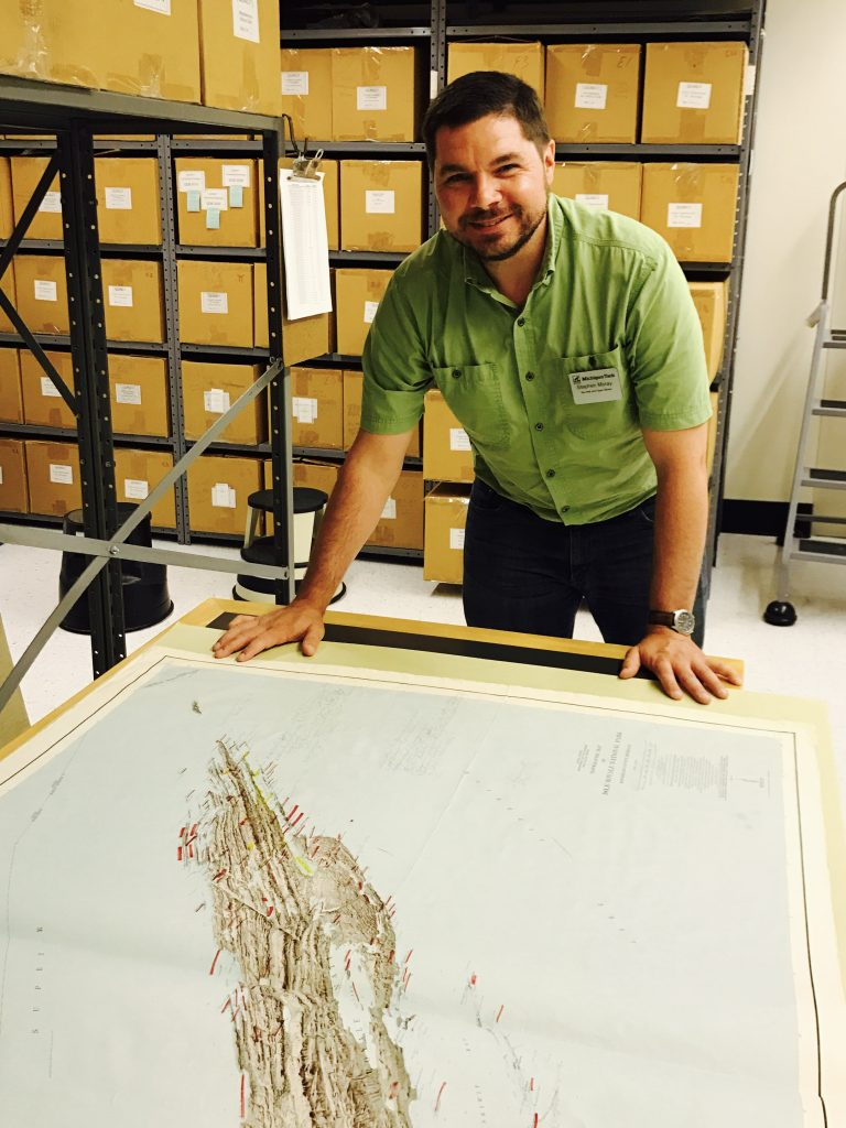 Steve Moray assesses a map of Isle Royale in the archives stacks.