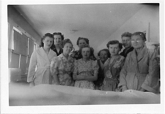A group of women being treated for tuberculosis at the Copper Country Sanatorium in 1950 pose for the camera in bathrobes and house dresses.