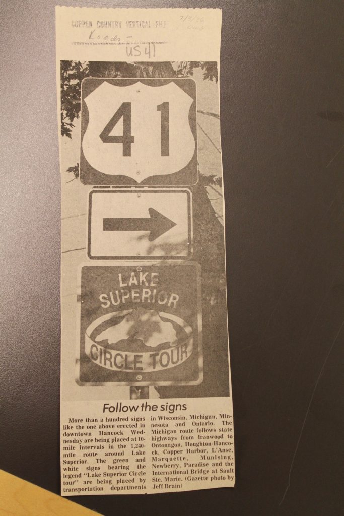 "Daily Mining Gazette article on installation of the first ""Lake Superior Circle Tour"" reassurance shield signage, from the Roads – US 41 folder, Copper Country Vertical Files, Michigan Technological University and Copper Country Archives."