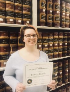 Becky poses with her certificate by the State Records Collection in the Archives stacks.