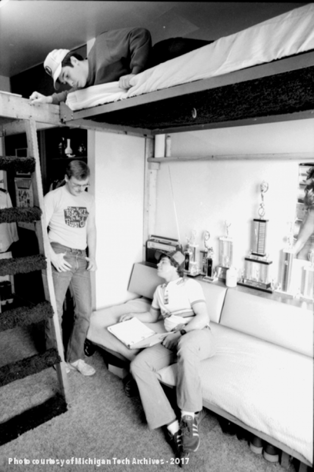 Three students relax in a dorm room, 1983.