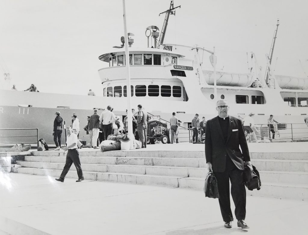 Priest in front of large boat