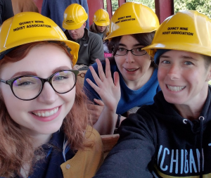 Three women are pictured in a tram car with hard hats on, preparing to descend into the mine tour.
