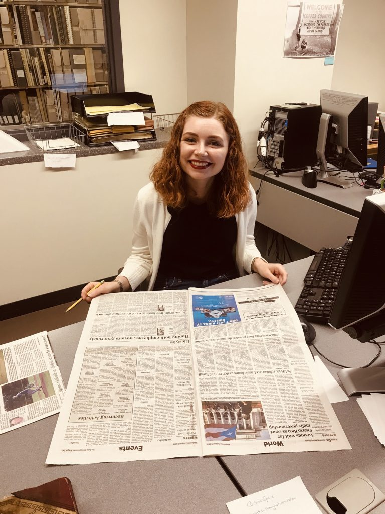 A young woman sits at a desk with a newspaper.