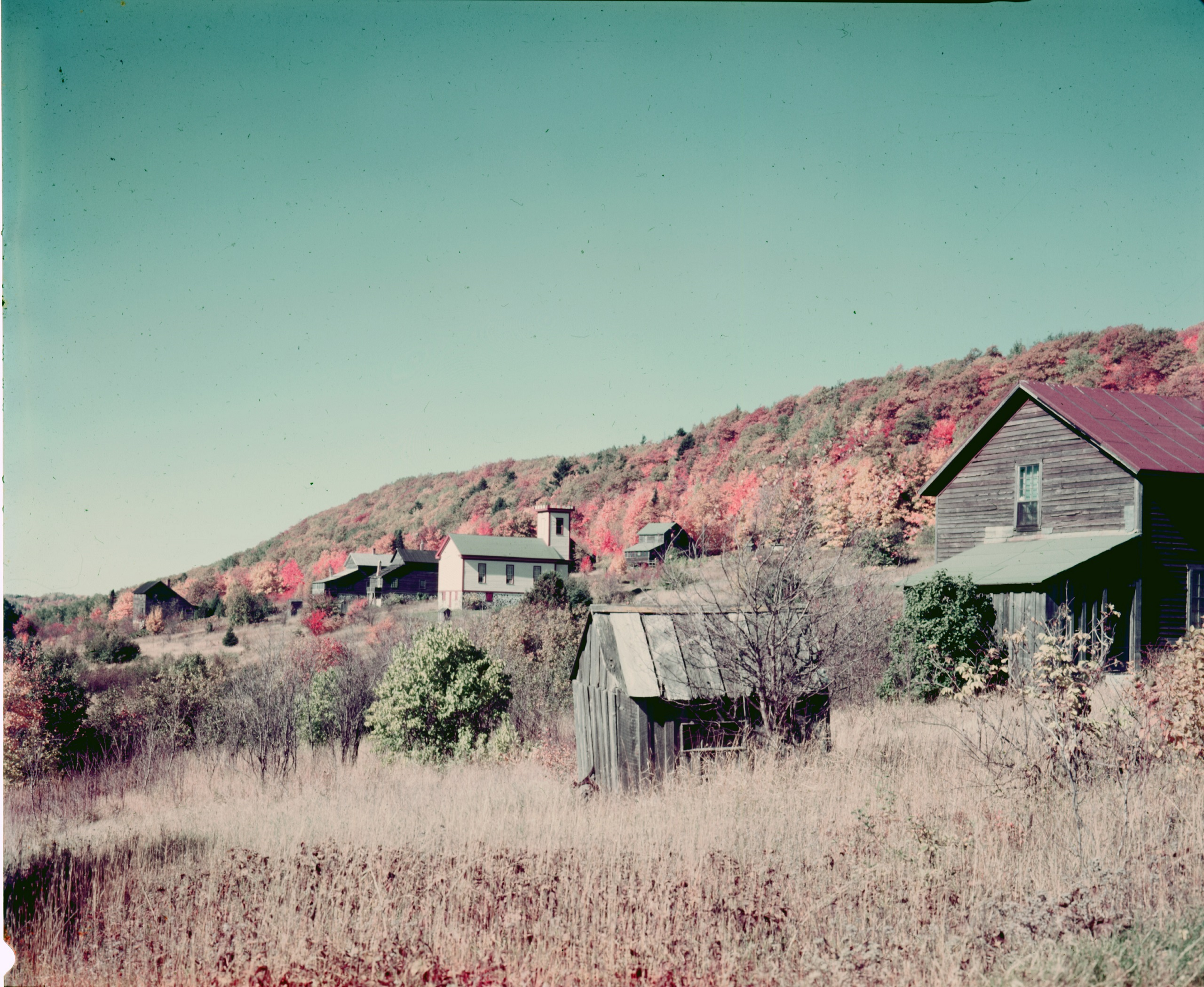 Photograph of old buildings on the hillside with fall colors.