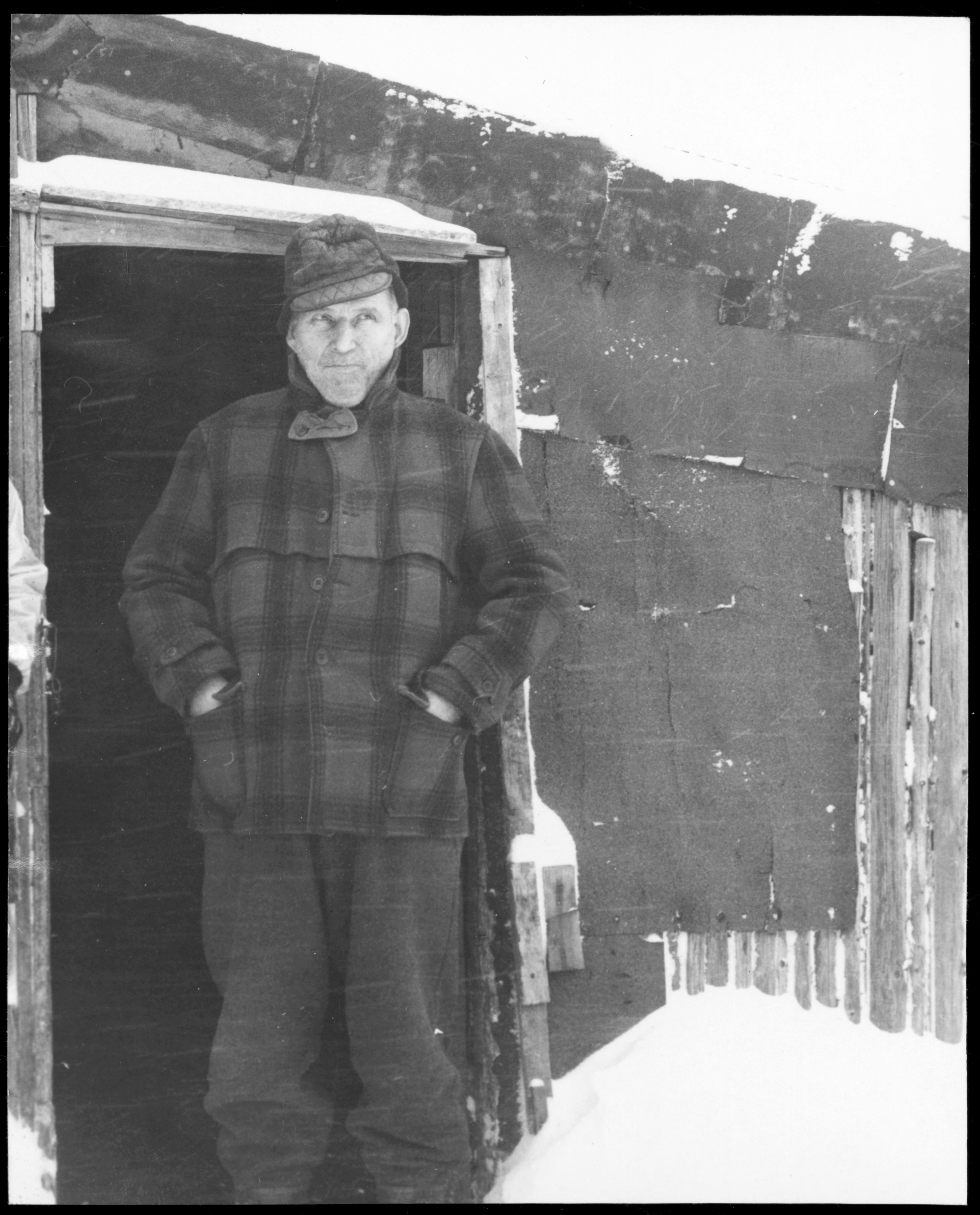 Man in plaid standing in front of cabin.