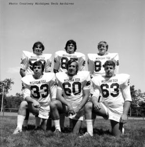 Michigan Tech football players pose on the field, 1974.