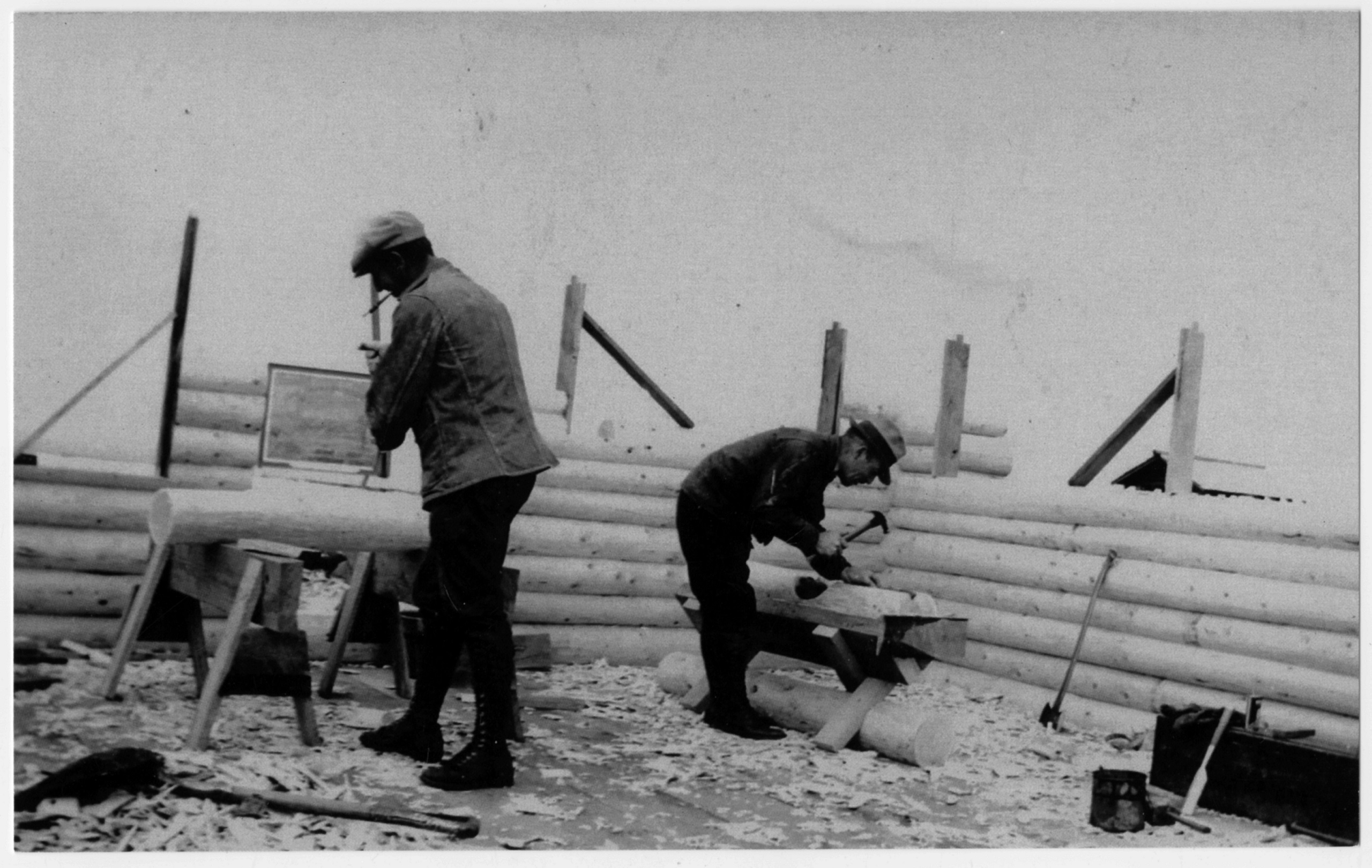 Two men working inside the frame of a log cabin