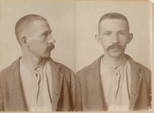 Mugshot of man with small mustace