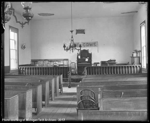 Image of plain church interior with central aisle and pump organ.