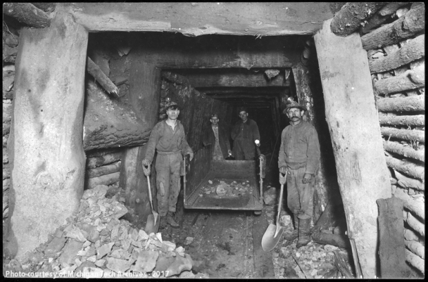 Group of men standing in a timbered mine level