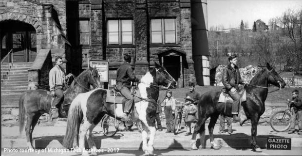 Three men riding horses on a city street