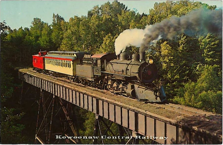 Train with locomotive, passenger car, and caboose passing over tall bridge