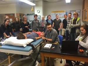 Michigan Tech students demonstrate arterial stiffness measurements to high school students.