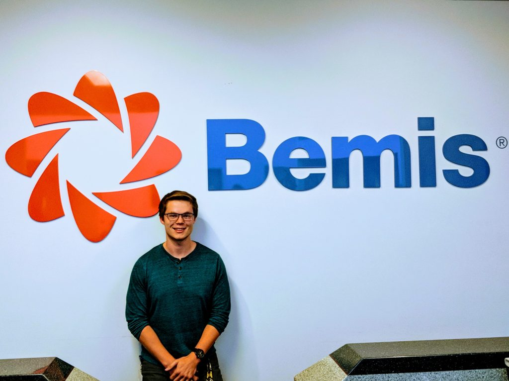 School of Business and Economics student Tom Strome stands in front of a Bemis sign/logo.