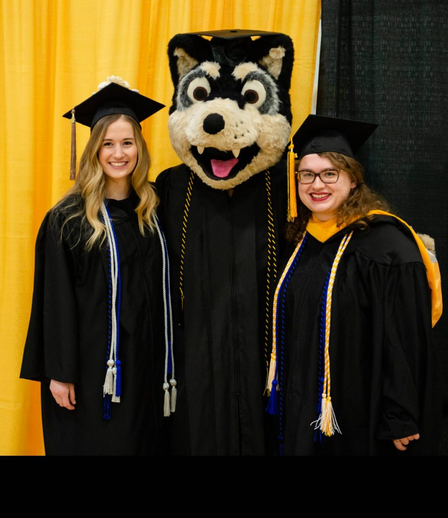 Two students flank mascot Blizzard during Commencement