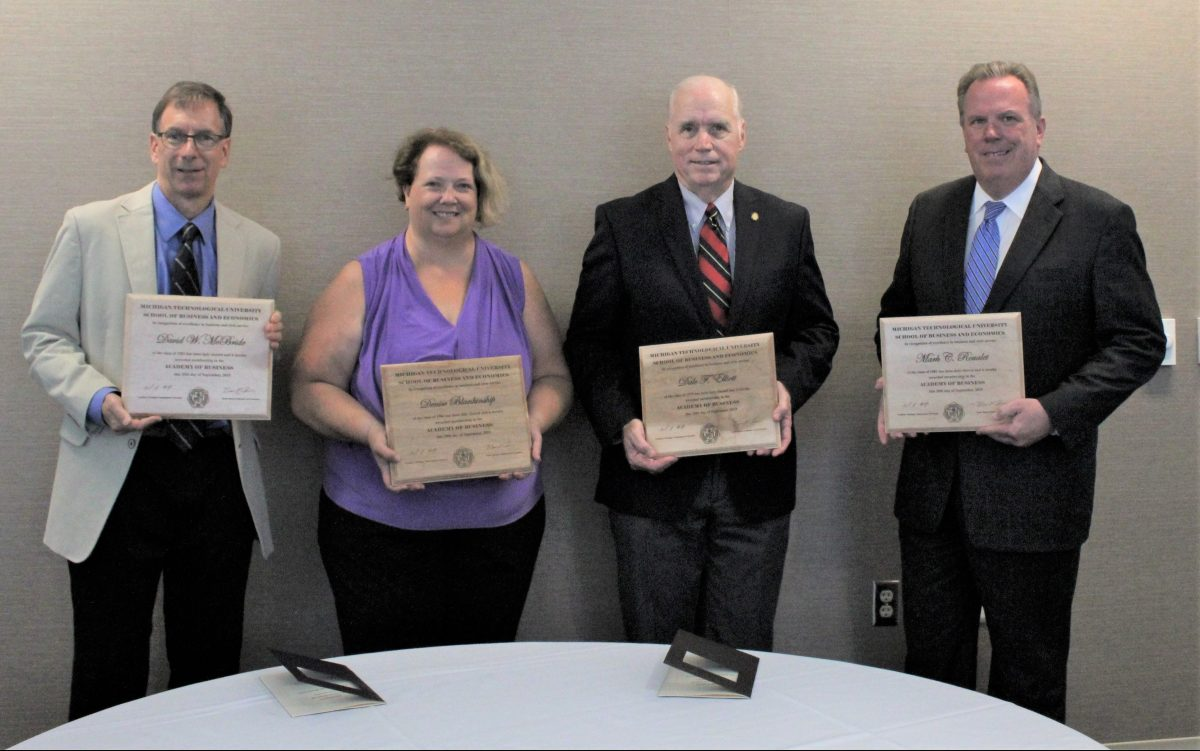Four people stand along wall with award plaques