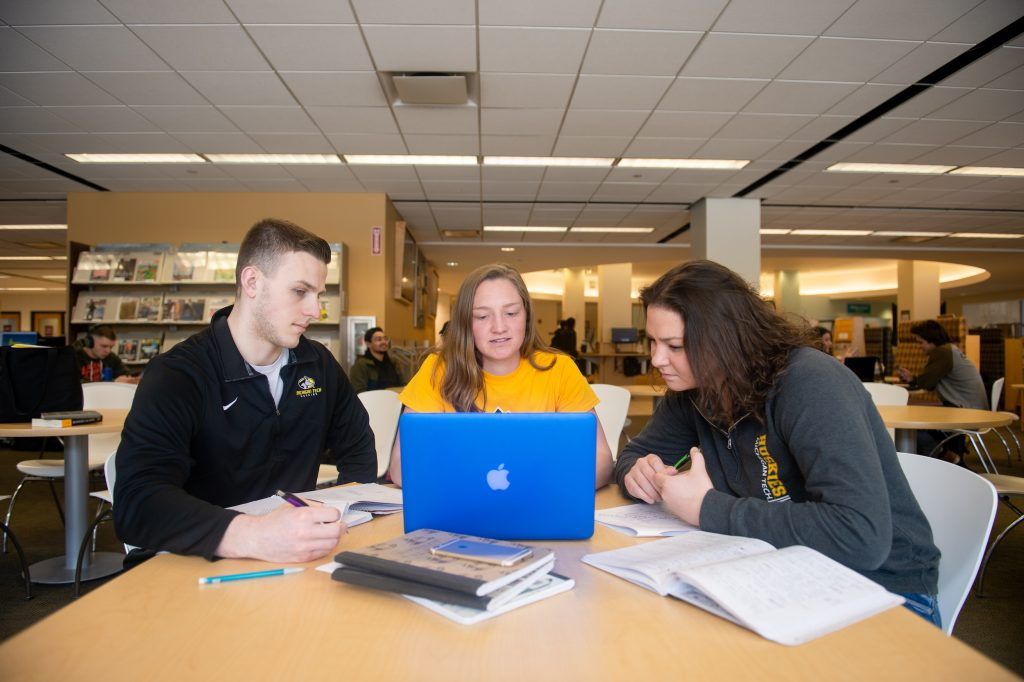Three students in library with Apple computer