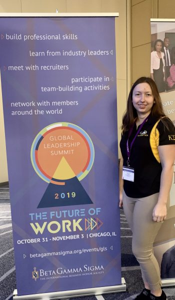Student stands in front of pull-up banner at conference