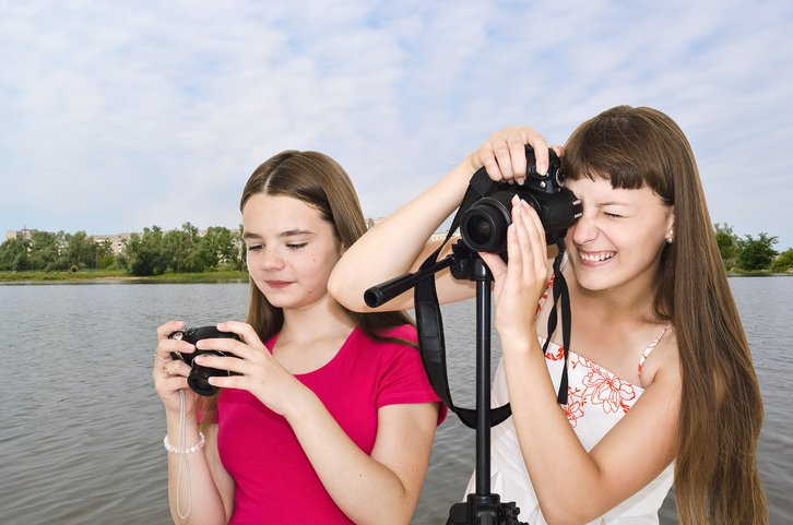 Two photographer teen girls outdoors by the river