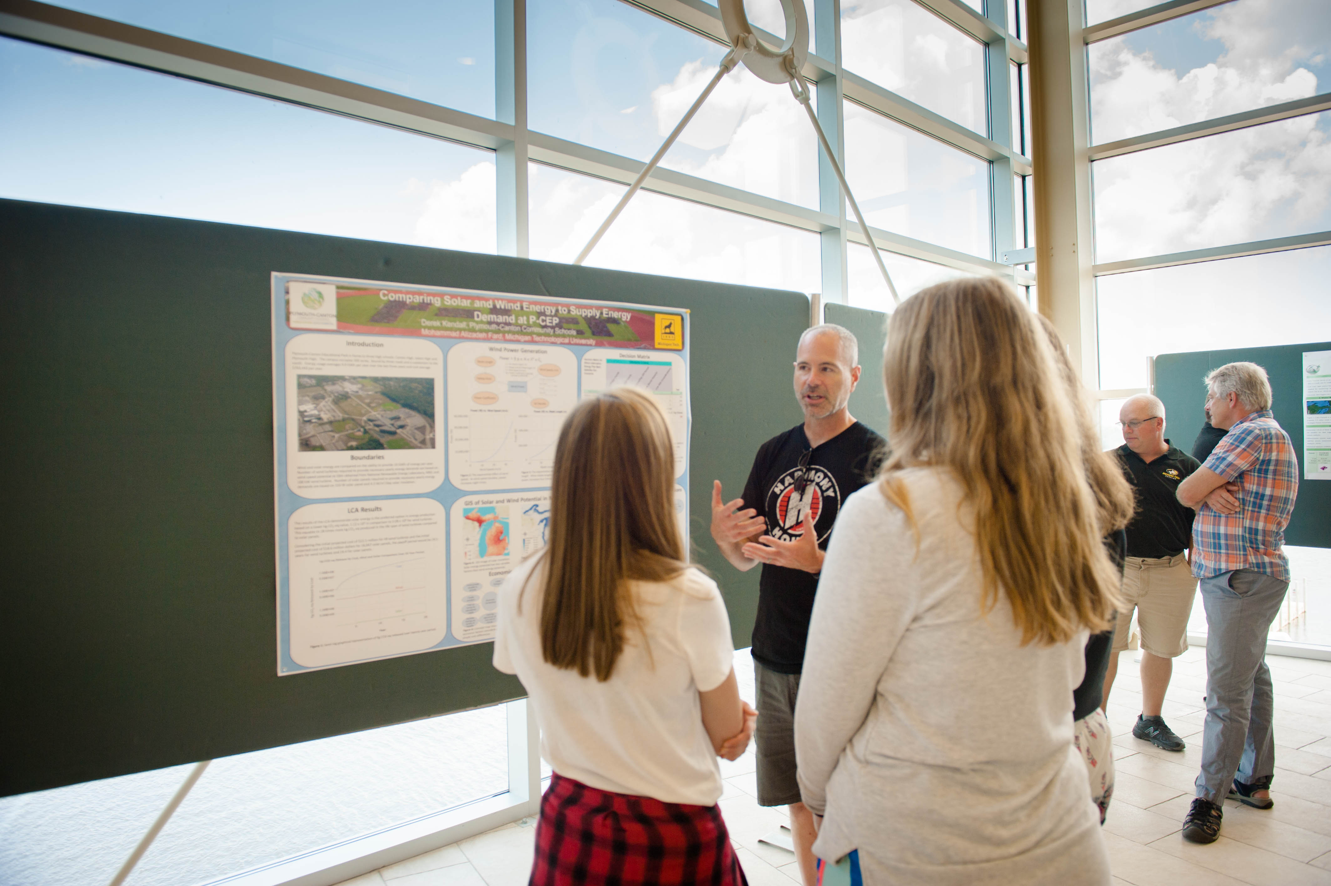 A poster presenter and two onlookers