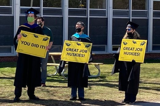 """Three faculty members with signs saying """"you did it"""" and """"congratulations."""""""