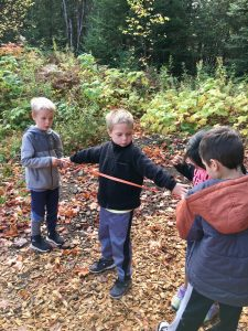 Young kids taking measurements in the woods