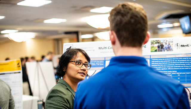Design Expo 2018 showing a person talking to a student at their poster