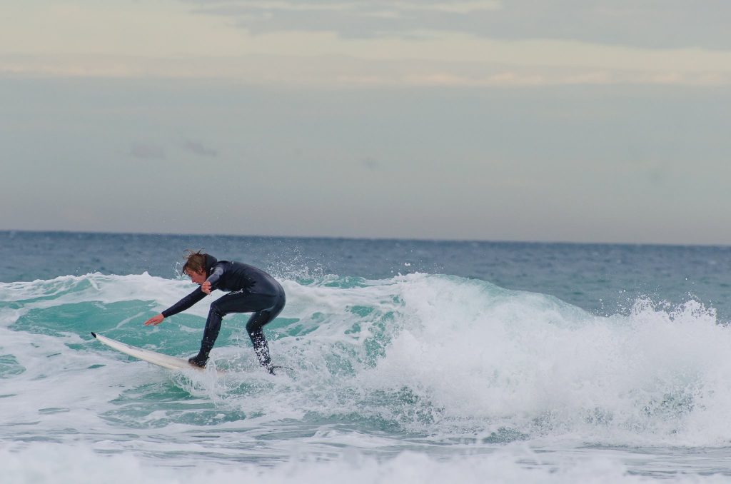 """Michigan Tech biomedical engineering student Mitch Kirby surfs in New Zealand. """"Traveling and living abroad while studying and working in the lab showed me that it is possible to mix work and play so that each day is an enjoyable one."""""""