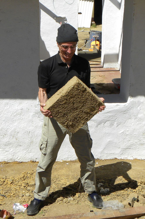 Brian Tucker of GeoHazards International (GHI) struggles to hold a heavy adobe brick used in typical buildings in rural Peru. GHI retrofitted an adobe school building in the village of Chocos, Peru, with geomesh, which holds the adobe walls together and greatly improves their earthquake resistance. Credit: Gregory Deierlein, Stanford University