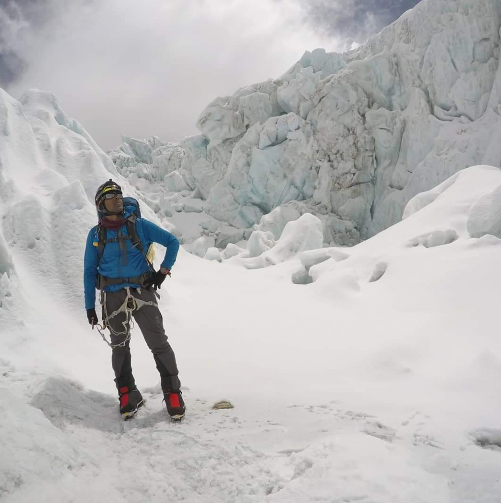 Sirak Seyoum stands in front of what seems to be a massive crevasse on his climb up Mount Everest