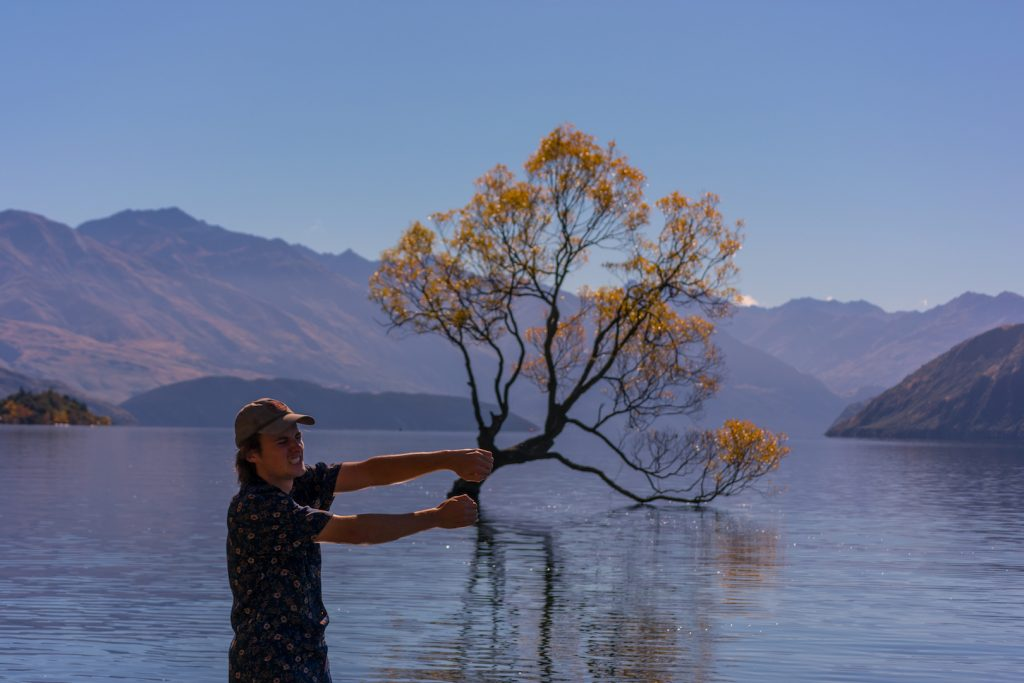 Ryan Schrader stands near the lake in Wanaka New Zealand. Behind him a leafy tree grows right up out of the lake.