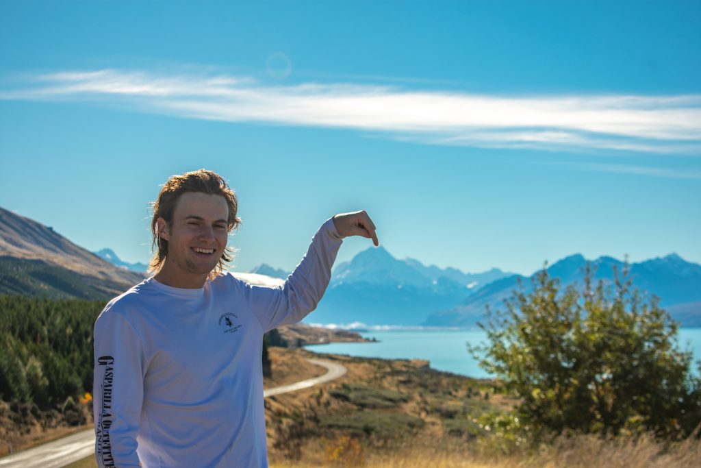 Ryan Schrader at the side of a winding mountain road, pointing at the mountain range in the background. His hand is curved and appears to touch the tip of the mountain.