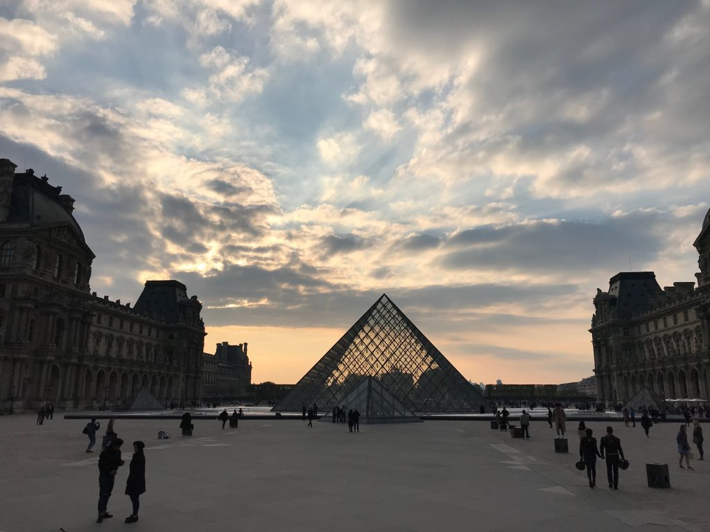 Main courtyard of the Louvre Palace in Paris with glass pyramid in view