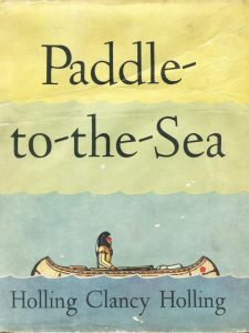 first edition book cover of Paddle-to-the-Sea, by Holling Clancy Holling, © 1941, renewed © 1969, Houghton Miffin showing an illustration of a Native American paddling a canoe in the aqua lake with a yellow variegated sky above.