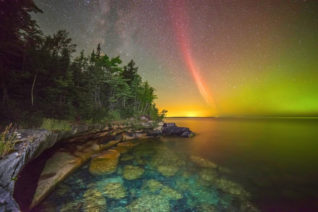 Proton arc, a rare, red type of aurora, over lake Superior. As the name indicates, proton arcs are caused not by electrons but by more massive protons that bombard the Earth's atmosphere following an energetic event on the Sun. Image won second place in the 2015 NOAA Weather in Focus Photo Contest. Photo credit: Ken Williams