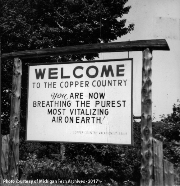 "Photo from the Daily Mining Gazette, August 1958 of a billboard in Houghton that says ""Welcome to the Copper Country. You are now breathing the purest, most vitalizing air on earth."""