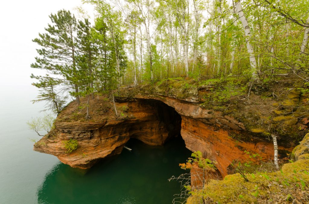 Apostle Islands Maritime Cliffs Wisconsin showing red orange cliffs, aqua blue green water, and trees growing from the cliff
